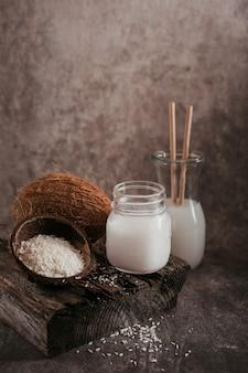 Бутылка кокосового веганского молока, кокосового масла, цельного кокоса и хлопьев на темноте