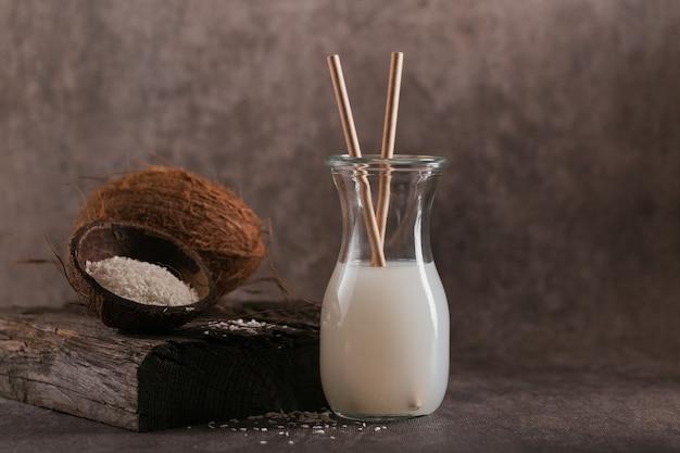 暗い背景にストロー、ココナッツ全体、フレークが入ったココナッツビーガンミルクのボトル。健康的なライフスタイルのコンセプト。