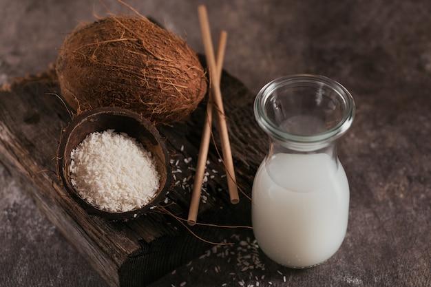 Бутылка кокосового веганского молока с соломкой, цельным кокосом и хлопьями на темном фоне