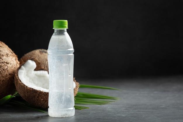 暗い背景に置かれたココナッツ水のボトル