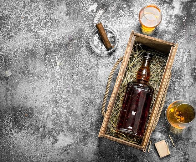 葉巻と古い箱に入ったコニャックのボトル。素朴な背景に。