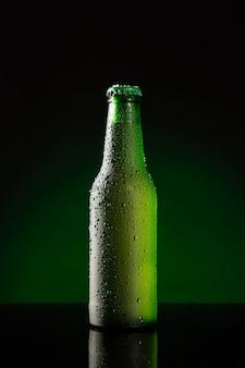 Бутылка холодного пива на темно-зеленом фоне. вертикальный формат.