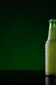 コピースペースと濃い緑色の背景に冷たいビールのボトル。垂直フォーマット。