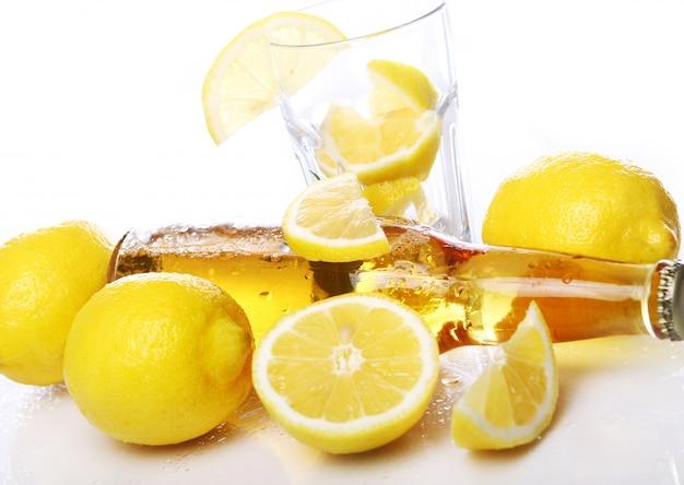 Бутылка холодного пива со свежими лимонами