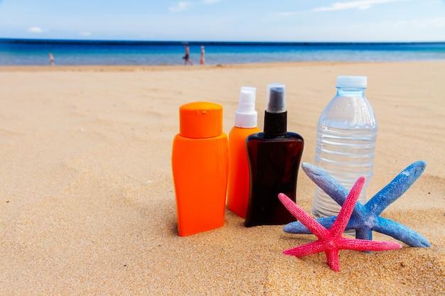 바다 쪽 모래 사장에 suntun 크림과 함께 시원한 물 한 병
