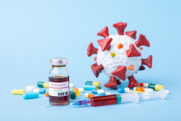 코로나 바이러스 백신 병, 파란색 테이블에 주사기