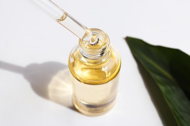 化粧品のエッセンシャルオイルと緑の葉の血清オイルのボトルがスポイトから滴り落ちています