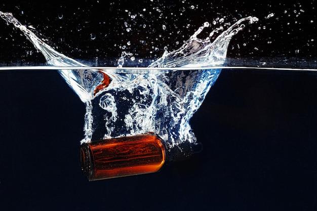 Бутылка косметической сыворотки в чистой прозрачной воде в темноте