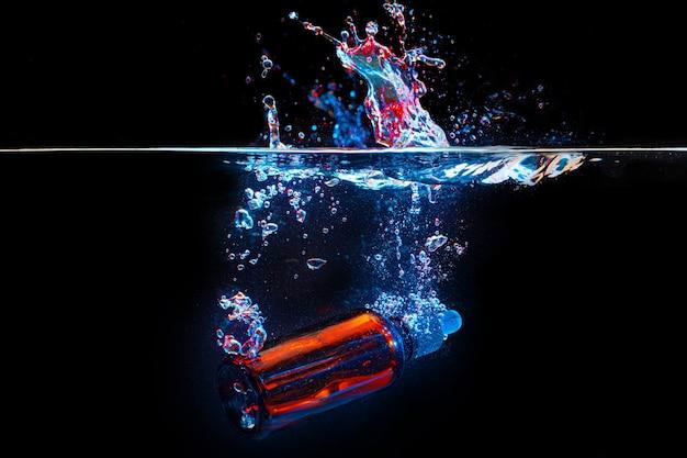 Бутылка косметической сыворотки в чистой прозрачной воде в темноте Premium Фотографии