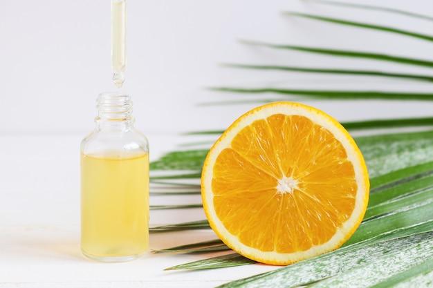 スポイトオレンジとヤシの葉の化粧品スキンケア美容液のボトル美容液がスポイトから滴り落ちています