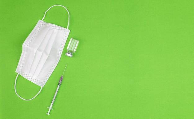Бутылка вакцины против коронавируса covid-19 и шприц на зеленом фоне с медицинской защитной гигиенической маской с местом для копирования справа. концепция распространения лекарства от вирусной эпидемии.