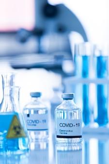 흐림 배경에서 실험실 장비와 실험실에서 covod-19 백신 샘플의 병. 코로나 바이러스 치료를위한 연구 및 실험실 테스트 아이디어.