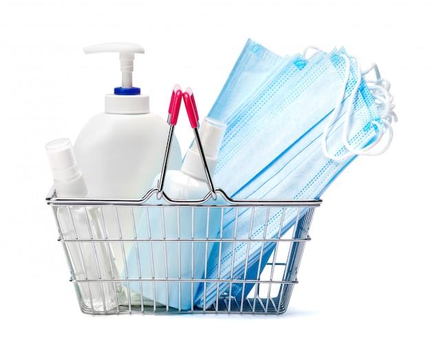 Бутылка крема, лосьона, дезинфицирующего средства или жидкого мыла и защитная маска в корзине на белом столе
