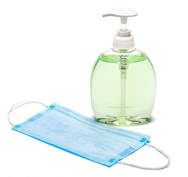 Бутылка крема, лосьона, дезинфицирующего средства или жидкого мыла и защитной маски на белом столе
