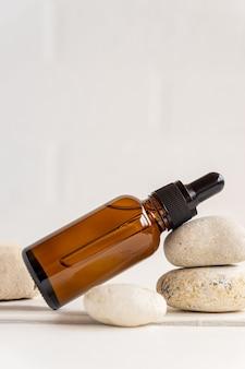 エッセンシャルオイルまたはフェイスセラムが入った濃い琥珀色のガラスのボトル。天然オーガニック化粧品、アロマテラピーマッサージオイル。テキスト用のスペースをコピーします。