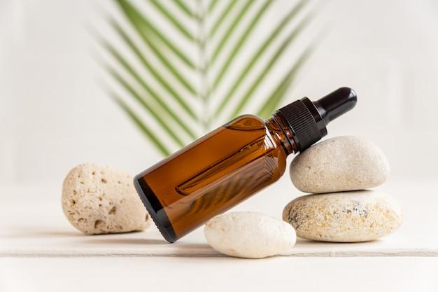 熱帯の葉の背景に天然石のスタックにエッセンシャルオイルまたはフェイスセラムと濃い琥珀色のガラスのボトル。