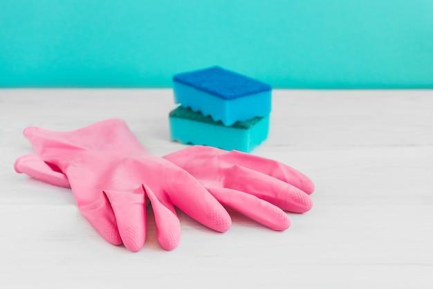 Бутылка для мытья посуды, губки и розовые резиновые перчатки на белом деревянном столе на зеленой стене