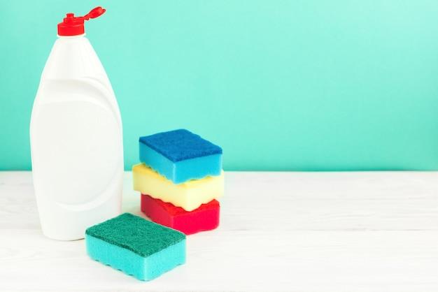 Бутылка для мытья посуды, губки, посуда на белом деревянном столе на зеленой стене