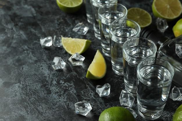Бутылка напитка, рюмки, кубики льда и ломтики лайма на черном дымчатом столе