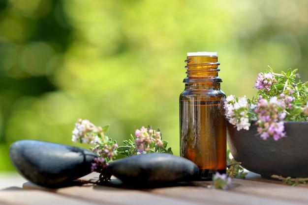 Бутылка эфирного масла и цветов ароматических трав и гальки на столе и на зеленой стене