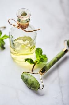 ミントと緑の葉のエッセンシャル オイルのボトルと顔用の翡翠のマッサージ ローラー化粧品のスキンケア ボディ ケア ビューティー ケアの概念のための天然有機成分