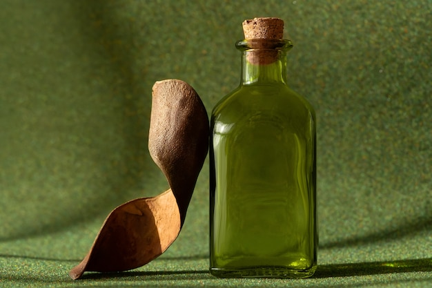 Бутылка эфирного масла на зеленом травяном фоне