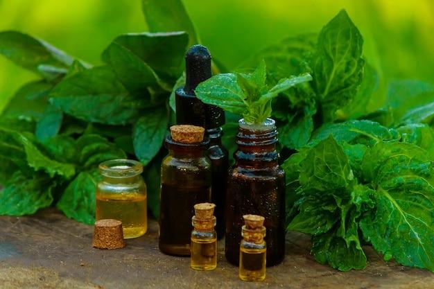 エッセンシャルオイルのボトルペパーミントと新鮮なミントの葉、暗いガラスの瓶にハーブの香り。切り株に。アロマテラピーのコンセプト。セレクティブフォーカス