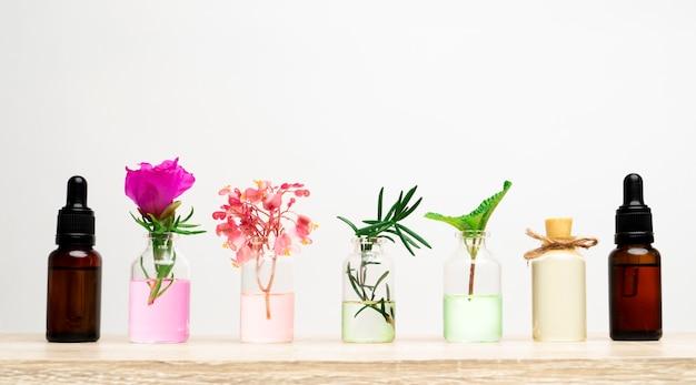Бутылка эфирного масла с травами, растениями и цветком