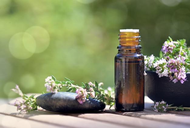 ラベンダーの花とテーブルにこぼれたエッセンシャルオイルのボトル