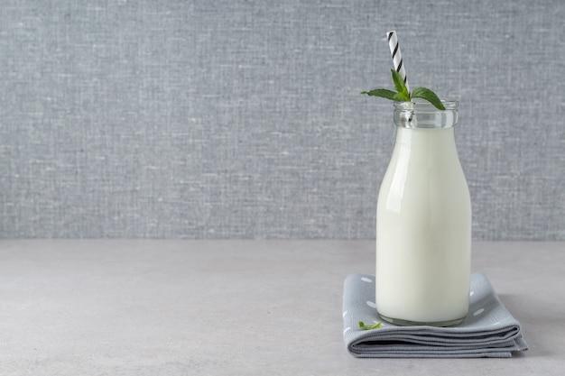 Бутылка ферментированного кефирного йогурта или айрана на сером столе домашний пробиотический молочный продукт