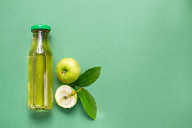 新鮮なリンゴジュースのフルーツパターンのボトルフラットレイトップビュー緑の背景とコピースペース