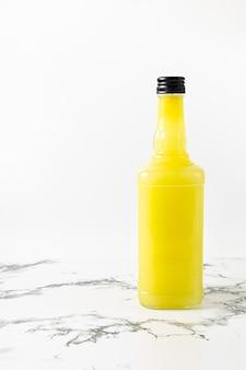 大理石のテーブルの上の白いプレートに新鮮なリモンチェッロのボトル
