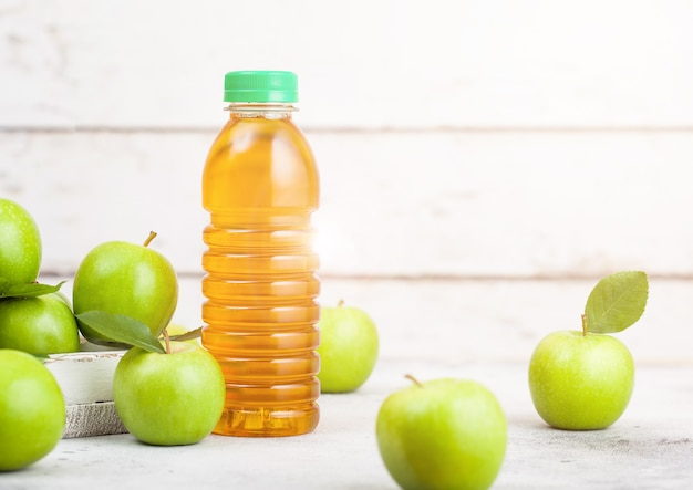 白い木製の背景に青リンゴと新鮮な有機リンゴジュースのボトル