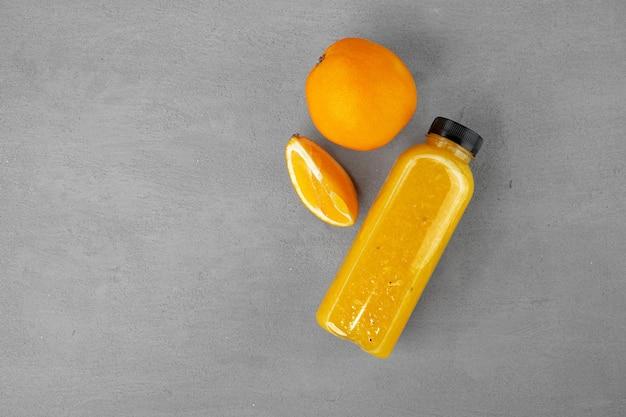 灰色の背景、コピースペースに絞りたてのオレンジジュースのボトル