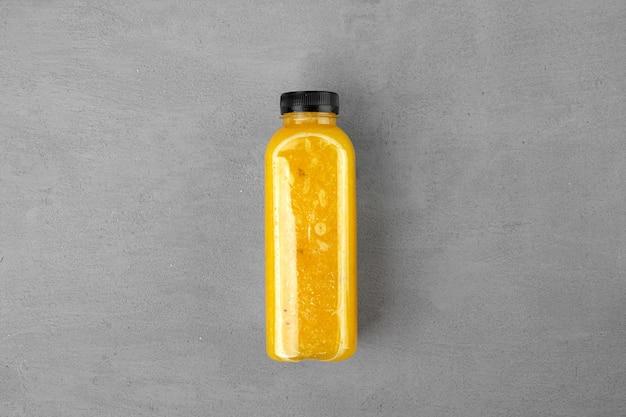 灰色の背景に絞りたてのオレンジジュースのボトル