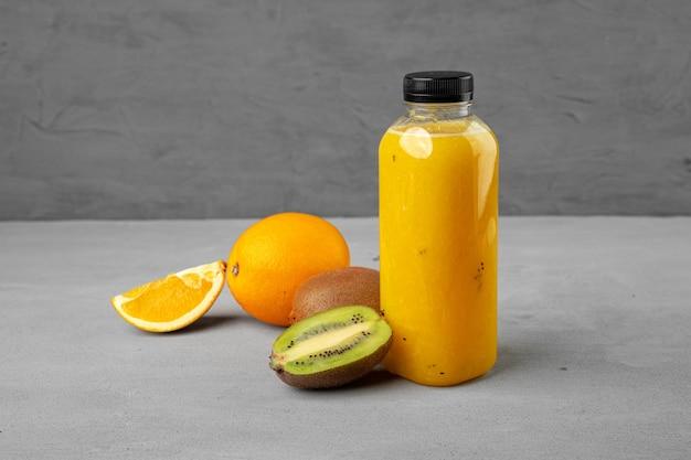 グレーに絞りたてのオレンジジュースのボトル