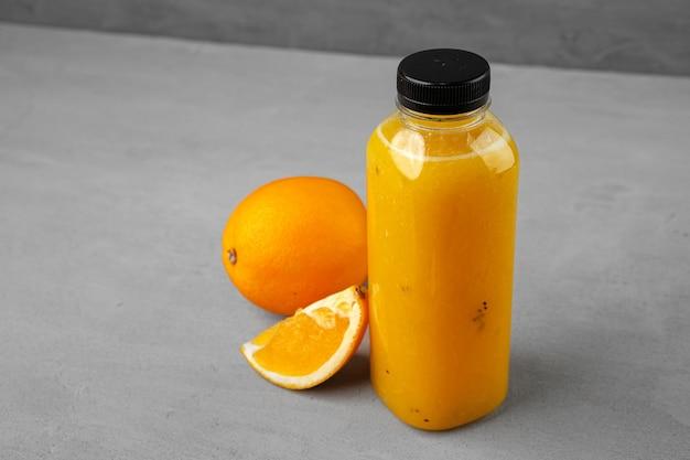 회색에 갓 짜낸 오렌지 주스의 병
