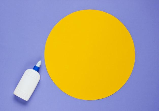 円で紫色の紙に接着剤のボトル