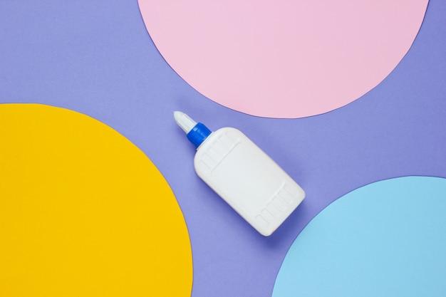 円の付いた紫色の紙に接着剤のボトル