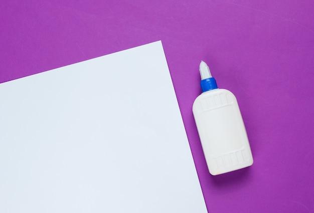 空白の紫色の紙に接着剤のボトル