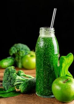 暗い壁に食材を使った緑のアルカリスムージーのボトル。