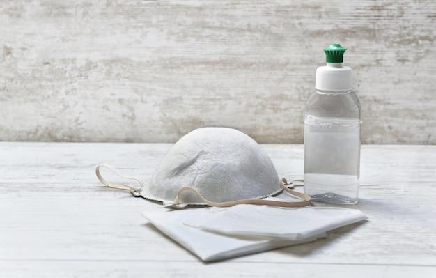 白い木製のテーブルの防塵マスクの横にあるハンカチに手の消毒剤のボトル