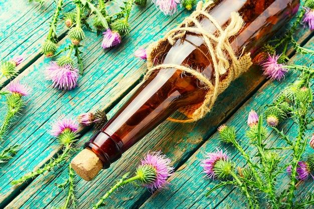 Бутылка лечебной травяной настойки на деревянных фоне. расторопша пятнистая или расторопша пятнистая в фитотерапии