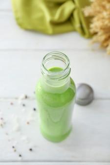 白いテーブルの上の健康的なスムージーのボトル