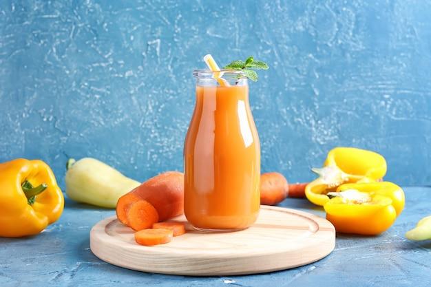 色の表面にニンジンとピーマンと健康的なスムージーのボトル