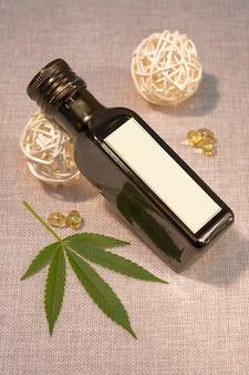Бутылка конопляного масла с листом каннабиса с капсулами