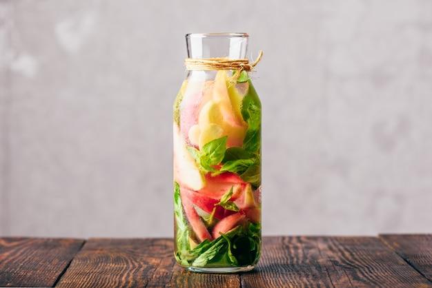 Бутылка настоянной воды с нарезанными листьями персика и базилика