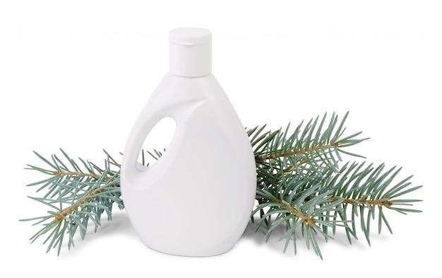 Бутылка жидкого мыла и еловые ветки на белом