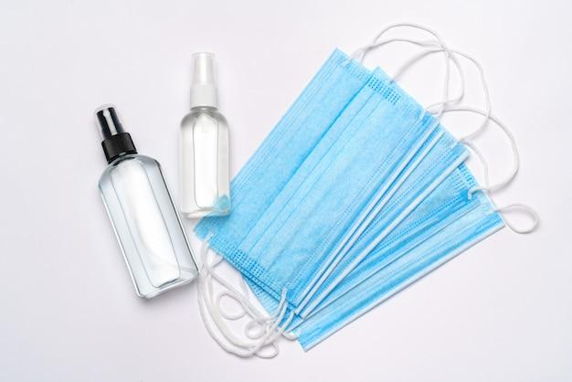 ローション、消毒剤または液体石鹸、薄い灰色の壁に分離された医療用防護マスクのボトル。