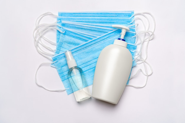 ローション、消毒剤または液体石鹸、クリッピングパスと白い壁に分離された医療用防護マスクのボトル。